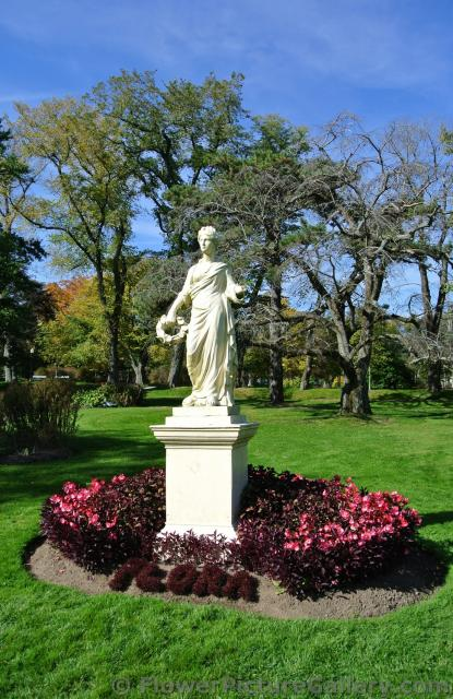 Roman woman statue surrounded by red leaves and flowers at Halifax Public Gardens.jpg