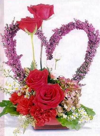Romantic Valentines Day center piece with roses and large purple heart shaped flowers.JPG