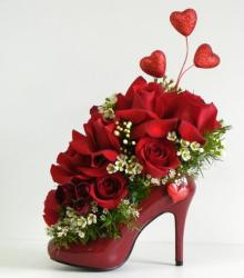Unique Valentines Day with red high heel shoe as a vase base filled with red roses and small white flowers.JPG