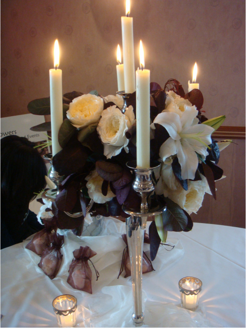 Chocolate brown wedding arrangement with long candles in white.PNG