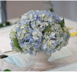 Reception table flower arrangement with blue white flowers.PNG