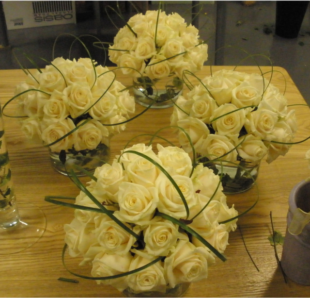 Wedding reception table arrangement with light yellow roses.PNG