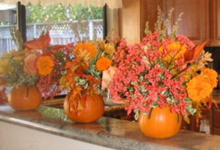 Beautiful Halloween centerpieces with fresh pumpkin as vases with red and orange flowers.JPG