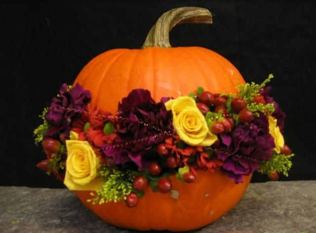 Fresh pumpkin with purple flowers and yellow flowers filled in the middle of pumpkin.JPG