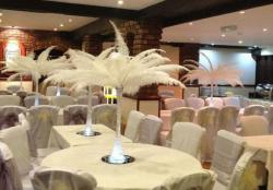 Wedding cheap centerpieces with white feathers in tall glass vases.JPG