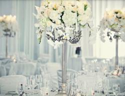 Wedding reception centerpices with white cream flowers and silver stands.JPG