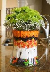 Fun Halloween centerpiece with vase filled with Halloween candies with green flowers and white flowers.JPG