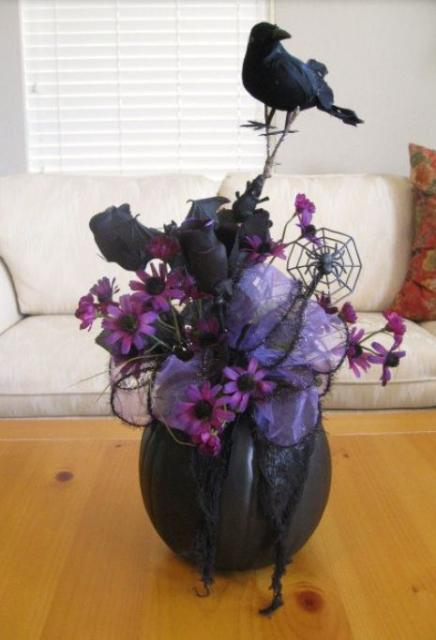 Witch theme flowers arrangement with purple flowers and black roses with a touch of halloween decor.JPG