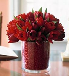 Red tulips in round short vase with red jelly beans