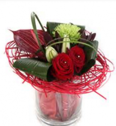 Modern valentines day arrangement with large leaves and red roses