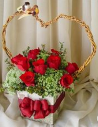 Unique valentines flowers gift basket with red roses and small white flowers with heart shape basket handle with two love birds