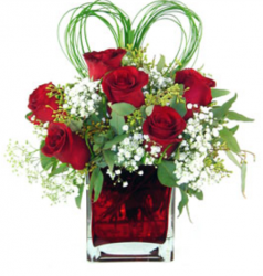 Valentines day arrangement with red roses and white small flowers with green leaves shape into heart