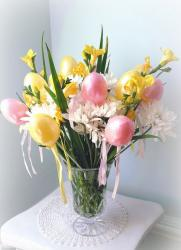 Cute Easter table arrangement with white and yellow spring flowers with pink easter eggs and yellow easter eggs