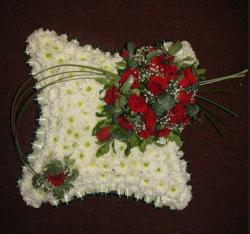 Fresh flowers shaped in pillow shape made with white daisies and red roses