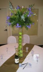 Tall wedding centerpiece with purple flowers and green apples inside the tall skinny vase