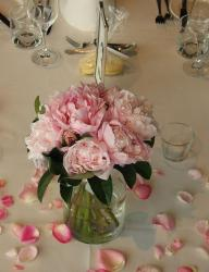 Trendy wedding arrangement with light pink flowers with flowers petals spreading around the vase