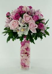 Beautiful pink wedding flowers arranement with flowers petals inside the tall glass vase