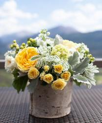 wedding arangement with white flowers and yellow flowers in tree vase