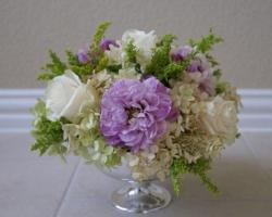 Elegant wedding arrangement flowers with white and purple flowers in silver vase