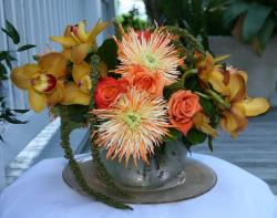 Elegant wedding centerpiece with orange flowers in silver vase