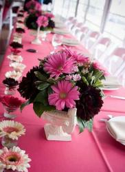 Beautiful wedding table setting with pink and dark red flowers and pink table cloth