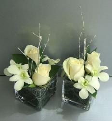 Chic short wedding centerpieces with white flowers and large green leaves