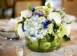 Elegant wedding center pieces with white flowers, green flowers and blueish flowers with green apple in water vase.PNG