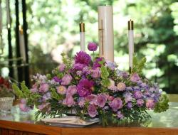 center pieces for a wedding with purple flowers and candals.jpg