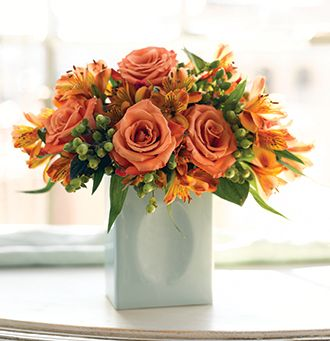 Light orange roses with bright orange flowers arrangement with green vase.JPG