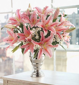 http://www.flowerpicturegallery.com/d/9700-1/Oriental+pink+lily+with+small+white+flowers+arrangement+with+elegant+silver+vase.JPG
