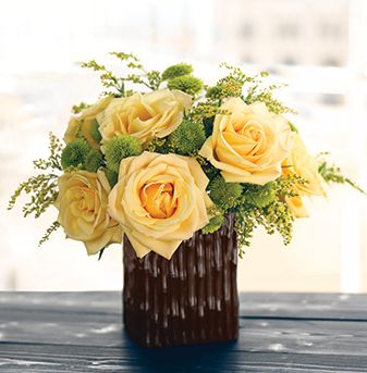 Summer arrangement with yellow roses and greens with brown vase.JPG